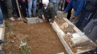This undated activist photo provided by the group Palestinians of Syria on Monday, Jan. 13, 2014 shows a funeral for a resident who died during the siege of the Palestinian neighbourhood of Yarmouk