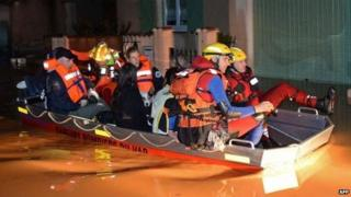 Rescue workers use a boat as they evacuate people from their homes in the Oratoire neighbourhood of Hyeres-Les-Palmiers on 19 January