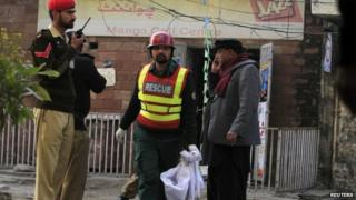 A rescue worker collects evidence from the site of a suicide blast in Rawalpindi, 20 January 2014