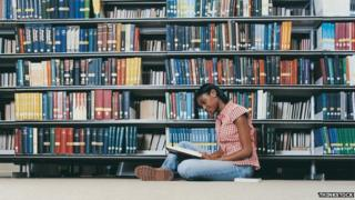 A student sitting on the floor at a library reading a book