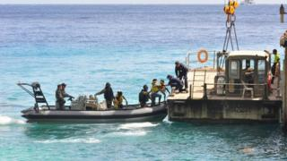 Suspected asylum seekers arrive at Christmas Island after being intercepted by the Australian Navy, on 3 August 2013