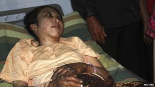 "Indonesian domestic helper Erwiana Sulistyaningsih lies in a bed whilst being treated at a hospital in Sragen, Indonesia""s Central Java province, 17 January 2014"
