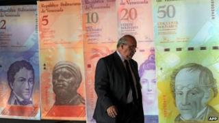 A man walk in front of posters of Venezuelan bills in Caracas