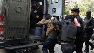 Man detained by police during clashes with pro-Morsi supporters in Nasr City, Cairo, on 17 January 2014