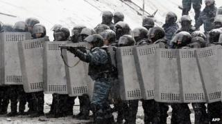 A riot police officer aims at demonstrators during clashes between protestors and police in the centre of Kiev on January 22, 2014.