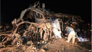 Pakistani Shia Muslims search the wreckage of a destroyed bus after a bomb attack 60 kilometres west of Quetta in Baluchistan on 21 January.
