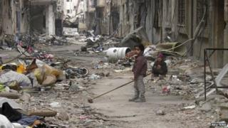 A child clears damage and debris in the besieged area of Homs on 26 January 2014