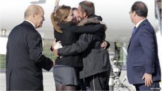 Former French hostage Daniel Larribe is welcomed by relatives as President Francois Hollande (far right) and Defence Minister Jean-Yves Le Drian look on