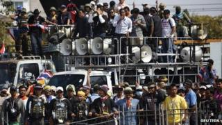 Anti-government protesters lock their arms as they stand at the gates of the Army Club in Bangkok on 28 January 2014.