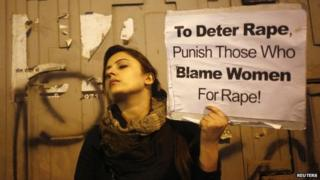 A demonstrator holds a placard as she attends a candlelight vigil to mark the first anniversary of Delhi gang rape, in New Delhi December 16, 2013.