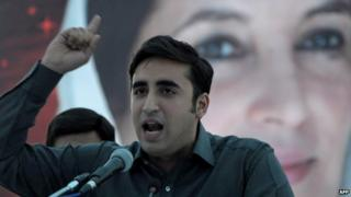 Bilawal Bhutto Zardari, the chairman of the Pakistan Peoples Party addresses supporters in front of a poster of his mother, slain Prime Minister Benazir Bhutto, at a rally in Karachi on 30 November 2013