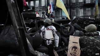 Anti-government protesters stand guard at a road bloc barricade in Kiev