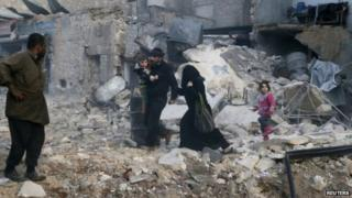 People walk on rubble of collapsed buildings at a site hit by what activists said was barrel bombs dropped by government forces in Aleppo's Dahret Awwad neighbourhood on 29 January 2014