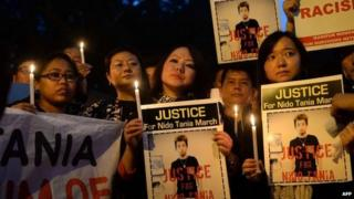 Indian students from the northeastern states and supporters hold placards and lit candles as they protest the death of northeastern student Nido Tania in New Delhi on February 2, 2014