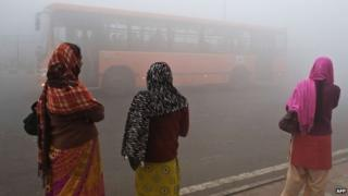 Indian commuters wait for a bus early on a polluted morning in New Delhi