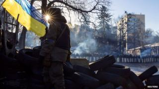 An anti-government protester stands on a barricade in Kiev, 3 February 2014
