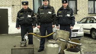 Belarusian police officials display seized distilling equipment