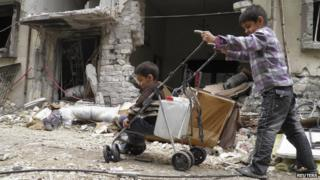 A boy pushes another on a pram along a damaged street filled with debris in the besieged area of Homs (2 February 2014)