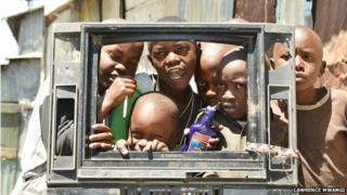 Children peeking through a broken TV set, copyright Lawrence Mwangi