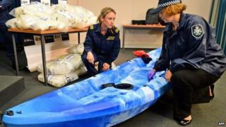 A customs officer (C) and a police officer (R) inspect one of the 27 kayaks seized after Australian authorities found A$180m of methamphetamine stashed in kayaks from China in Sydney on 12 February 2014