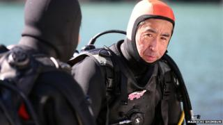 Yasuo Takamatsu listens to his diving instructor