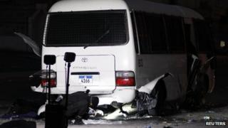 A police special unit inspects the police patrol mini bus which was hit by explosions at a police checkpoint in the village of Dih