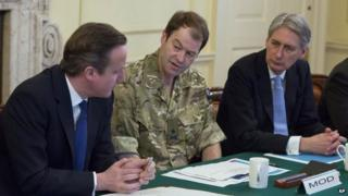 Prime Minister David Cameron, left, chairs a government emergency meeting, as he speaks with Major General Patrick Sanders, centre, and Defence Secretary Philip Hammond, right, at 10 Downing Street