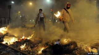 Protestors walk through wreckage in Caracas on 19 February, 2014.