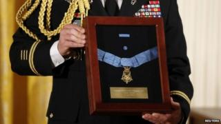A US Army officer holds a medal case before President Barack Obama presents the Medal of Honor posthumously to the nephew of US Army Chaplain (Captain) Emil Kapaun, for heroism during the Korean War while in the East Room of the White House, 11 April 2013