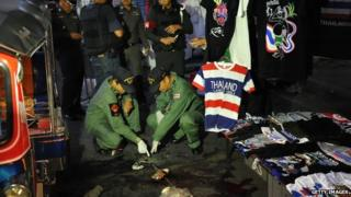 Bomb squad police examine the scene of a deadly explosion at an anti-government rally on 23 February 2014 in Bangkok