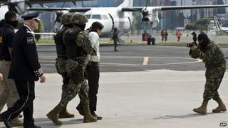 Joaquin Guzman is escorted by marines on 22 February, 2014 in Mexico City