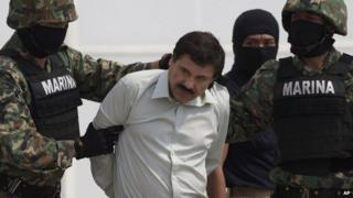 Joaquin Guzman is escorted to a helicopter in handcuffs by Mexican navy marines at a navy hanger in Mexico City on 22 February