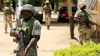Nigerian soldiers stand guard at the offices of the state-run Nigerian Television Authority in Maiduguri, Nigeria on 6 June 2013