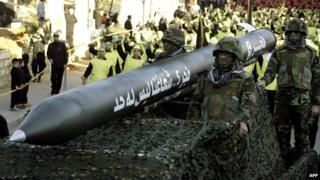 Hezbollah fighters ride on a vehicle carrying a Fajr 5 missile during a parade in the Lebanese town of Nabatiyeh on 28 November 2012