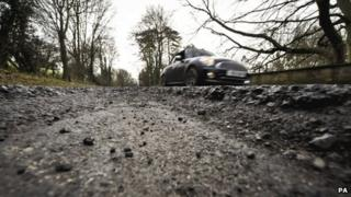 A car on a heavily potholed road in Gloucestershire