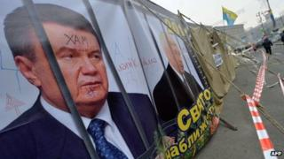 A placard depicting Ukraine's then President Viktor Yanukovych and Prime Minister Mykola Azarov behind prison bars at the protesters' camp in Maidan (Independence) Square in Kiev on 27 December 2013