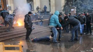 Pro-Russian protesters drag away a wounded man during clashes with rival protesters in Kharkiv on 1 March 2014