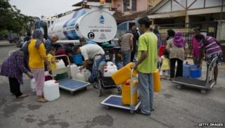People collecting water from a tank in Malaysia