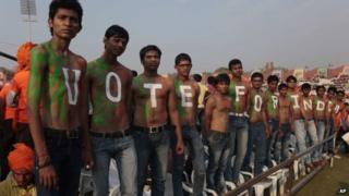 """Supporters of India""""s opposition Bharatiya Janata Party (BJP)""""s prime ministerial candidate Narendra Modi stand with their bodies painted at a youth convention in Ahmadabad, India."""