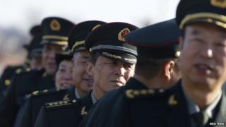 Military delegates from the Chinese People's Liberation Army gather outside the Great Hall of the People for a plenary meeting of the National People's Congress in Beijing, 4 March 2014
