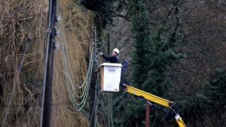 Engineer works on repairing electricity power lines near Reigate in Surrey after floods hit the area