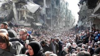 A vast crowd of people queue for aid at the Yarmouk refugee camp near Damascus