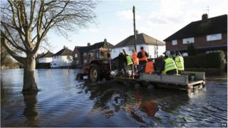 Tractor and trailer pass through flooded street in Egham