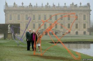 Irish artist Michael Craig-Martin (centre) discusses his giant umbrella sculptures with the Duke and Duchess of Devonshire at Chatsworth House, their stately home