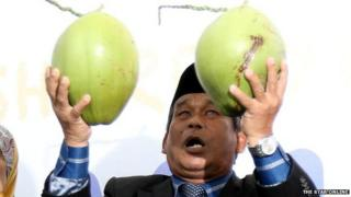 "A Malaysian ""Bomoh"" holding two pieces of fruit"