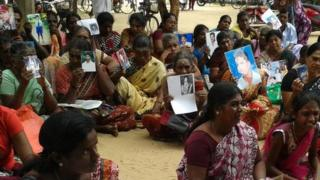 Tamil women hold up pictures of their missing relatives