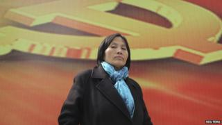 Prominent Chinese human rights activist Cao Shunli stands in front of an emblem of the Chinese Communist Party during an interview in the central business district of Beijing 23 March 2013