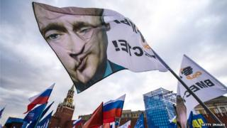 Pro-Kremlin activists wave a flag depicting President Vladimir Putin at rally at the Red Square in Moscow, on 18 March 2014, to celebrate the incorporation of Crimea
