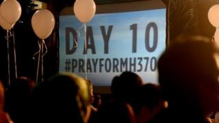 "A slide projection reads ""Day 10"" at a rally for the missing Malaysian Airlines plane at a Kuala Lumpur area shopping mall."