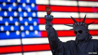 A person dressed up in a Statue of Liberty in front of a US flag